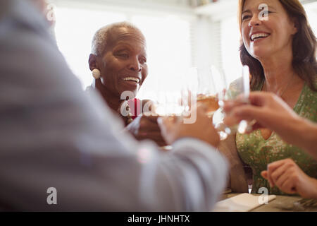 Smiling mature women drinking wine, dining at restaurant - Stock Photo