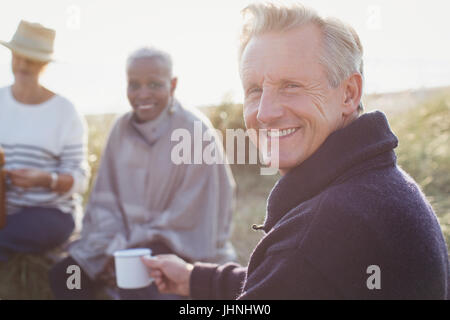 Portrait smiling senior man drinking coffee with friends on sunny beach - Stock Photo