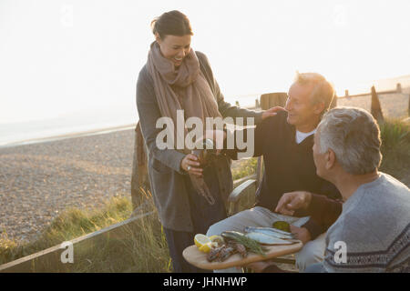 Mature friends drinking wine and enjoying barbecue on sunset beach - Stock Photo