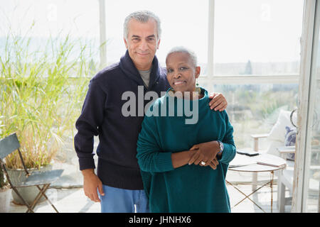 Portrait affectionate senior couple on beach house sun porch - Stock Photo