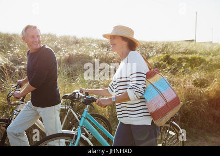 Mature couple walking bicycles on sunny beach grass path - Stock Photo