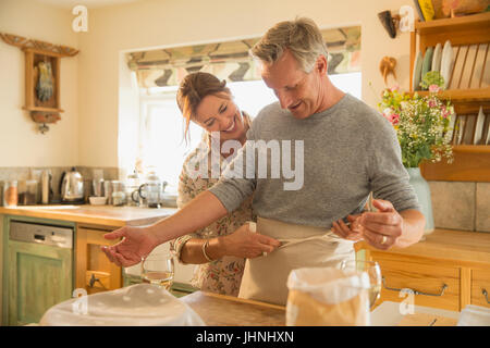 Playful mature couple baking, putting on apron in kitchen - Stock Photo