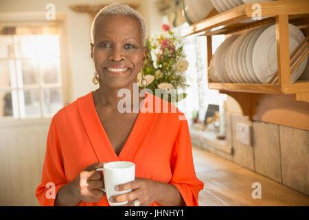 Portrait smiling senior woman drinking coffee in kitchen - Stock Photo