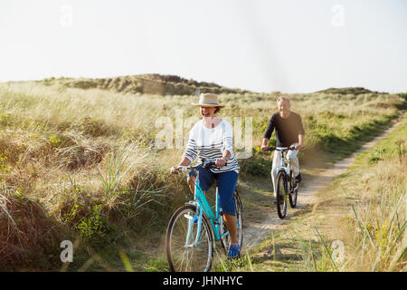 Mature couple riding bicycles on sunny beach grass path - Stock Photo