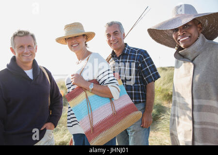 Portrait smiling mature couples on sunny beach - Stock Photo