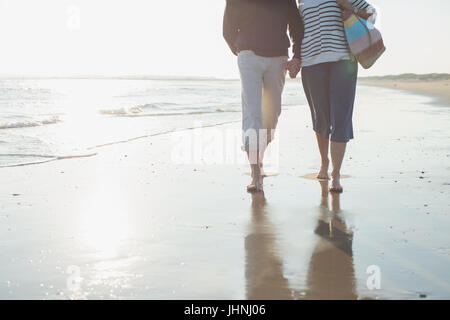 Affectionate barefoot mature couple walking, holding hands in sunny ocean beach surf - Stock Photo