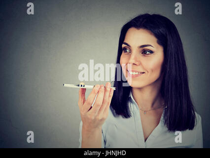 Girl using a smart phone voice recognition function on line isolated on gray wall background - Stock Photo