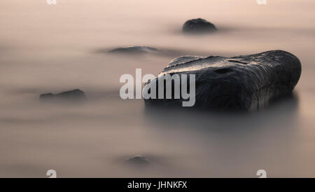 stone in the misty water - Stock Photo