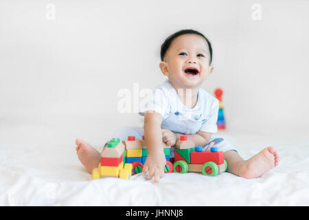 Adorable Asian baby boy 9 months sitting on bed and playing with color wooden train toys at home. - Stock Photo