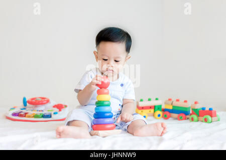 Adorable Asian baby boy 9 months sitting on bed and playing with color developmental toys at home. - Stock Photo