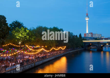 People in Spree riverside at museum island, with the television tower in the background - Stock Photo