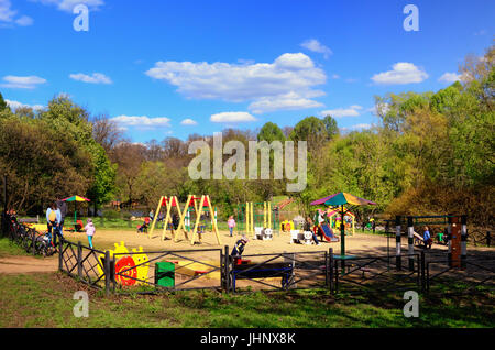 Children's Playground in a Green Park in May with Kids Playing and Parents - Stock Photo