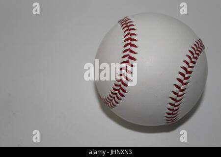 Baseball with red stitches on white background - Stock Photo