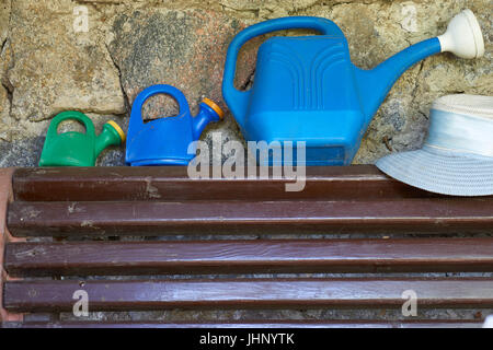 three different size of plastic watering cans for gardering and woman's summer hat on a brown wooden bench besides - Stock Photo