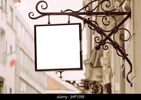 Blank square signboard, hanging from wrought iron bracket, in the city, classic architecture buildings background. - Stock Photo