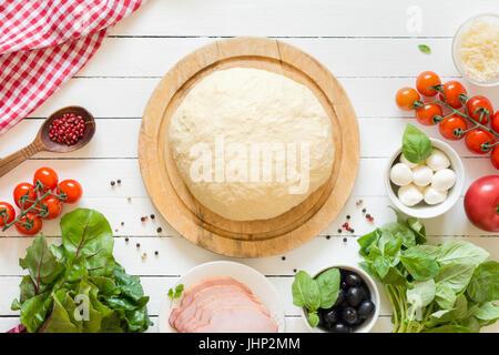 Prepared pizza dough and ingredients on white wooden background. Cherry tomatoes, basil, ham, mozzarella cheese, - Stock Photo