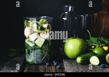 Ingredients for healthy green smoothie in blender cup. Fresh organic fruits and vegetables: cucumber, apple, spinach, - Stock Photo