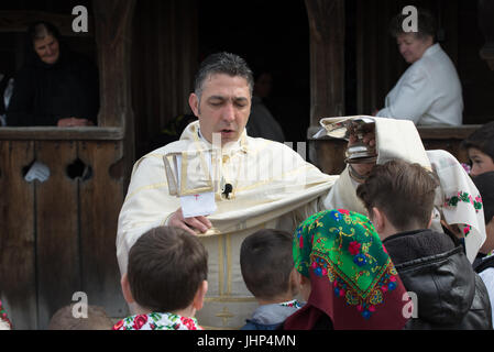 Orthodox priest blessing people in traditional costume at 'Udatoriul' old agrarian custom on Easter Monday, Surdesti, - Stock Photo