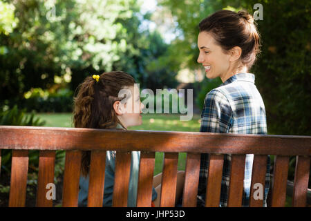 Smiling mother and daughter sitting on wooden bench in backyard - Stock Photo