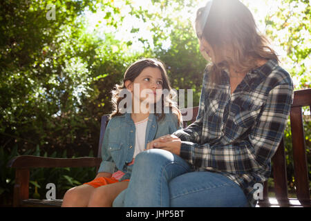 Girl sitting with mother on wooden bench against trees at backyard during sunny day - Stock Photo