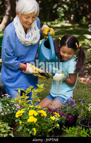 Smiling girl and grandmother watering plants in backyard - Stock Photo