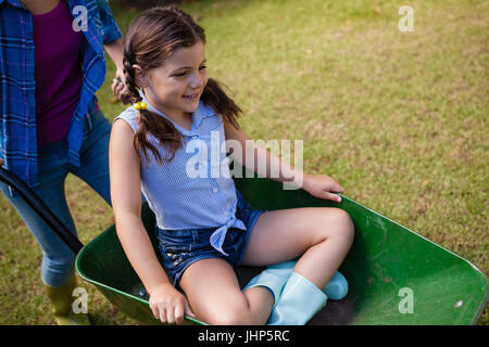 High angle view of mother pushing smiling daughter sitting in wheelbarrow at backyard - Stock Photo