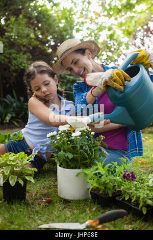 Happy mother with daughter watering potted plants while sitting on field in backyard - Stock Photo