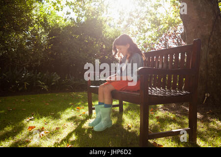 Smiling girl using smart phone while sitting on wooden bench in backyard during sunny day - Stock Photo