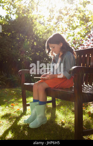 Full length of girl using phone while sitting on wooden bench in backyard during sunny day - Stock Photo