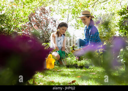 Smiling mother with daughter looking at potted plants while sitting on grassy field in backyard - Stock Photo