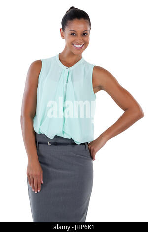 Smiling businesswoman standing with her hand on hip against white back - Stock Photo