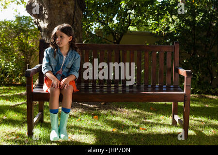 Girl wearing casual sitting on wooden bench at garden - Stock Photo