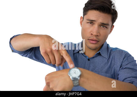Portrait of businessman showing time against white background - Stock Photo