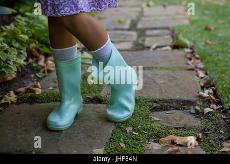 Low section of girl wearing green rubber boots standing on walkway at backyard - Stock Photo