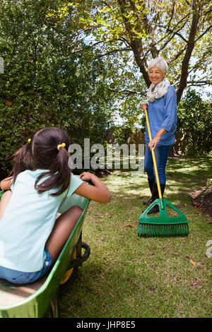 Grandmother holding rake while looking granddaughter sitting in wheelbarrow at backyard - Stock Photo