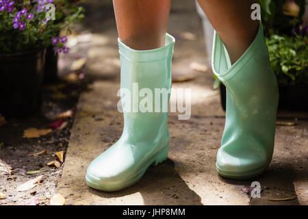 Low section of girl wearing green rubber boot standing on footpath at backyard - Stock Photo