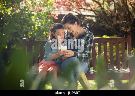 Girl showing mobile phone to mother while sitting on wooden bench at backyard - Stock Photo