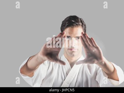 Digital composite of Portrait of martial arts Man with grey background - Stock Photo