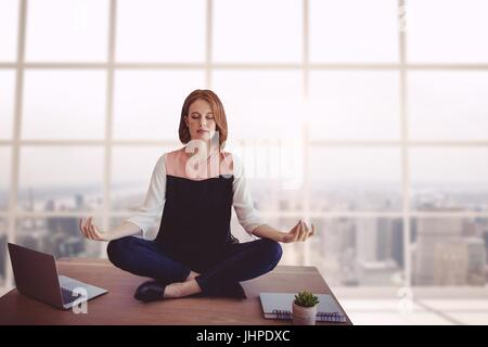 Digital composite of Business woman on a desk meditating - Stock Photo