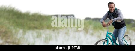 Digital composite of Middle aged man on bicycle against sand dune - Stock Photo