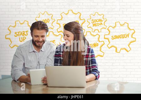 Digital composite of Happy business people at a desk looking at a tablet and a computer against white wall with - Stock Photo