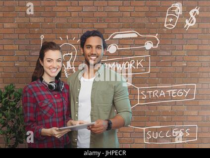 Digital composite of Happy business people holding a tablet against brick wall with graphics - Stock Photo