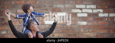 Digital composite of Father with son on shoulders against blurry red brick wall - Stock Photo