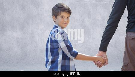 Digital composite of Father and son holding hands against grey wall - Stock Photo