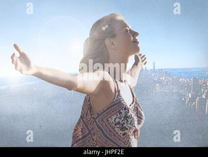 Digital composite of Woman with open arms practicing casual mindfulness in front of city - Stock Photo