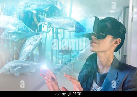 Woman watching big fish in an aquarium stock photo for Virtual reality fishing