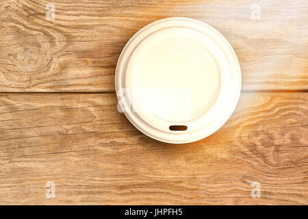 Overhead of cup over white background against brown wood panelling - Stock Photo