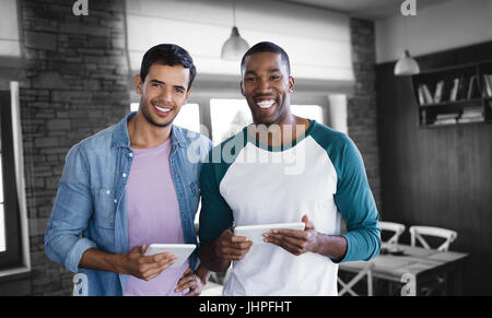 Smiling businessmen are using a digital tablet against empty chairs and tables - Stock Photo