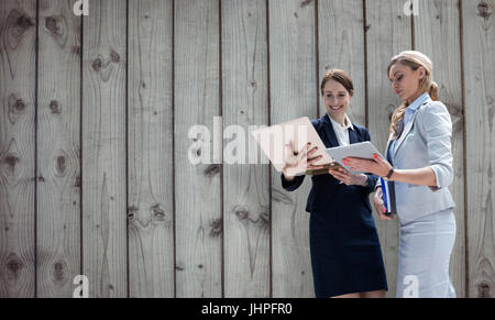 Smiling business women using digital tablet against close-up of wooden fence - Stock Photo