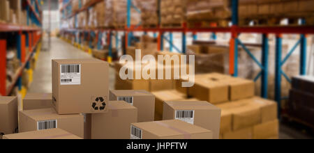 Group of composite cardboard boxes against boxes on pallet by rack - Stock Photo